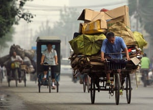 Beijing, China: A rubbish collector pedals his tricycle loaded with cardboard and plastic bottles to a recycling centre located near the northern outskirts of the city. Photograph: David Gray/Reuters