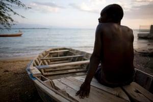 Port-au-Prince, Haiti: A fisherman takes a rest on his boat at Ibo beach. Photograph: Alexandre Meneghini/AP