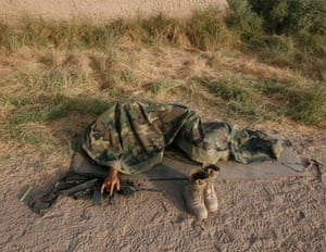 Helmand province, Afghanistan: A US Marine from the 24th Marine Expeditionary Unit asleep on the ground in the town of Garmser.  Photograph: Rafiq Maqbool/AP