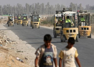 Gaza strip: Palestinian forklift trucks on their way to the Sufa border post to unload trucks carrying goods from Israel. Supplies have been arriving after Israel and Hamas agreed a truce three weeks ago. Photograph: Adel Hana/AP