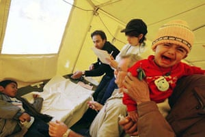 January 2 2003, Bam, Iran: A child cries as an other child is treated by doctors at the American field hospital