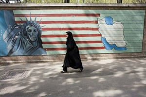 April 18 2007, Tehran, Iran: A girl passes a mural at the former US embassy