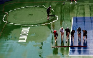 Workers wipe the court during a rain delay