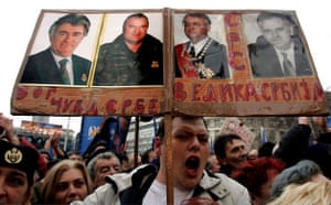 February 2006, Belgrade, Serbia: A Radical party supporter holds photos of war crimes suspects Radovan Karadzic, Ratko Mladic and Vojislav Seselj at a rally