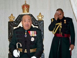 King George Tupou V, sits on his throne