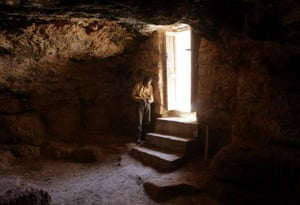 A Jordanian archeologist stand by the entrance of the cave