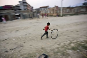 A Nepalese boy runs as he plays with a wheel