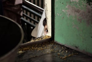 A young boy waits for free rice provided at the Bari Imam Shrine
