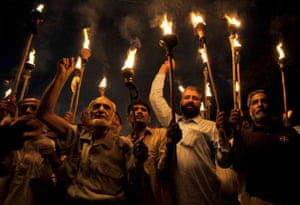 Activists from Pakistani labour Unions hold lighted torches during a march