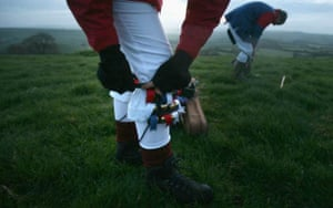 A Priston Jubilee Morris Man adjusts his bells as he prepares to dance at dawn at the locally known One Tree Hill