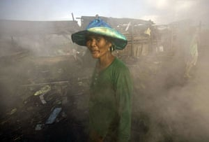 Manila, Philippines: A woman walks past an area where charcoal is made by residents of a garbage dump