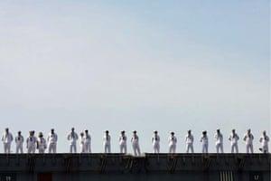 Yokosuka, Japan: Crew members stand on deck on board the nuclear-powered US aircraft carrier USS George Washington at Yokosuka Naval Base
