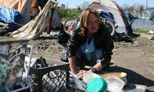 Carol Carlile washes dishes outside her tent