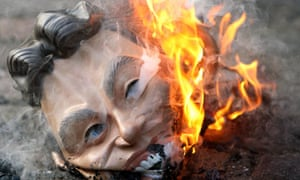 A demonstrator burns a mask of Tony Blair outside the Chilcot Iraq inquiry