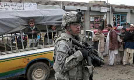 Villagers watch as US army patrol in Aghanistan.