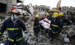 Iraqi rescue workers evacuate a body at the scene of a bomb blast in Baghdad