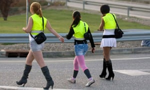 Prostitutes touting for work at the roadside outside Lleida, Spain, wearing high visibility vests.