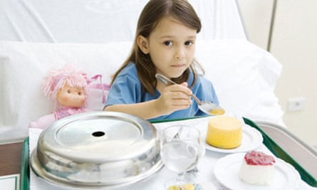 Girl eating meal in hospital bed