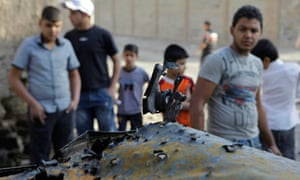 Iraqis inspect a destroyed car at the scene of a bomb attack on Christian houses in Baghdad.