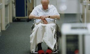 Elderly patient in a wheelchair on a hospital ward