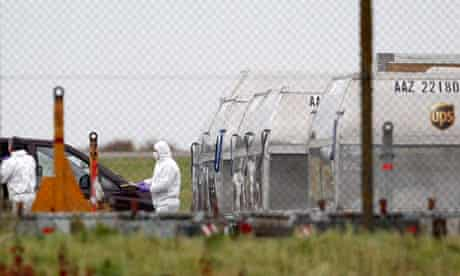 A forensic officer removes a package from a UPS container at East Midlands Airport