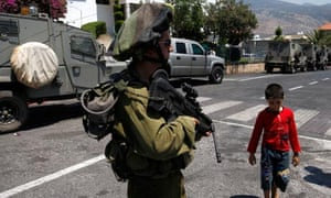 Israeli soldier stands guard in Ghajar on the Israeli-Lebanese border