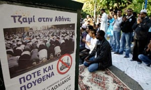 muslims in athens pray behind a party poster reading 'mosque in athens: nowhere and never'