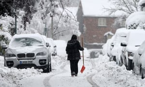 woman walks in snow carrying shovel