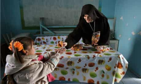 Sister Marie Benedict gives food to Mongolian orphan at soup kitchen in Ulan Bator