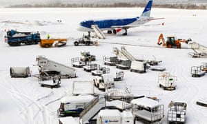 A plane and airport vehicles are covered in snow