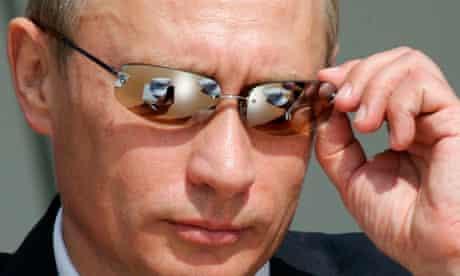 Russian President Vladimir Putin adjusts
