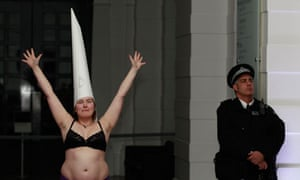 A demonstrator holds her arms up during a protest at the Tate Britain