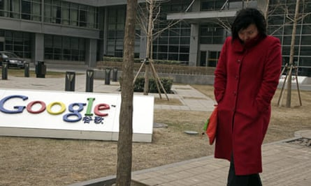 A Chinese woman walks past the Google logo at the Google China headquarters in Beijing, China