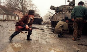Chechen rebels take cover behind a tank during street fighting in Grozny in 1995.
