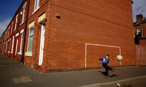 A young boy playing football in Salford