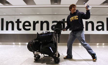 A passenger waves as he arrives from Vancouver on the first flight in five days at Heathrow Airport