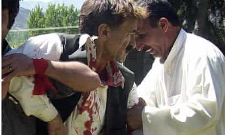 Help for an injured man after a bomb attack on a political rally in Timergarah, Pakistan