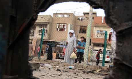 Iraqi People, seen through a shrapnel hole, inspect the site of a car bomb attack in Baghdad
