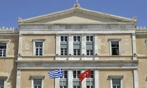 Greek and Turkish flags fly at the Greek Parliament