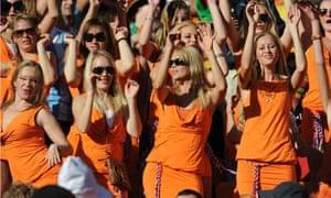 36 women dressed in orange minidresses