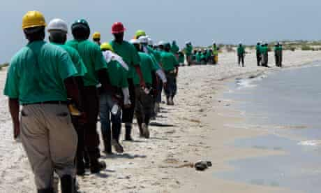 Oil cleanup workers hired by BP walk along the beach in Dauphin Island