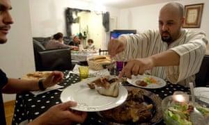 Shop owner Bensalem serves food for Iftar meal in his flat in Geneva