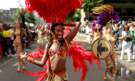 A costumed reveller performs in the Notting Hill Carnival in London
