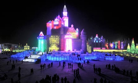 Tourists look at ice sculptures in Harbin