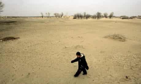 little boy walking on dry barren desert land