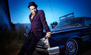 Tom Waits photographed sitting against the hood of a car