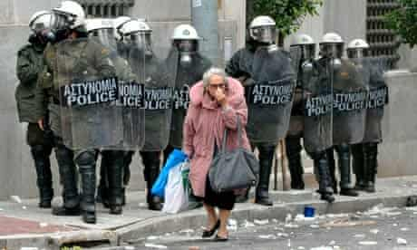 A woman walks past riot police during protests in Athens, December 2010.