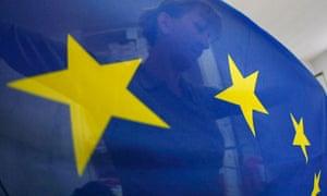 A seamstress sews a European Union (EU) flag in a small workshop in Belgrade