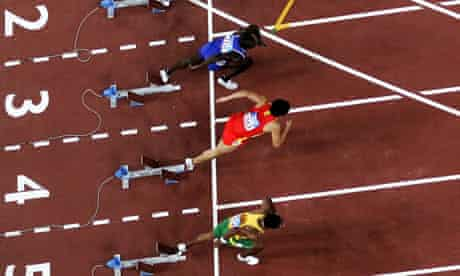 Athletes in the mens 110 metre hurdles sprint off the starting blocks