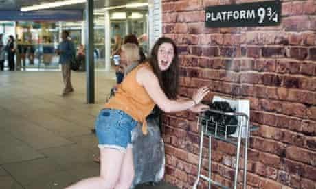 A Harry Potter fan visits  Platform 9 ¾ at King's Cross station.